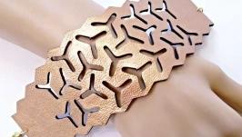 Широкий ажурный кожаный браслет бронзового цвета.