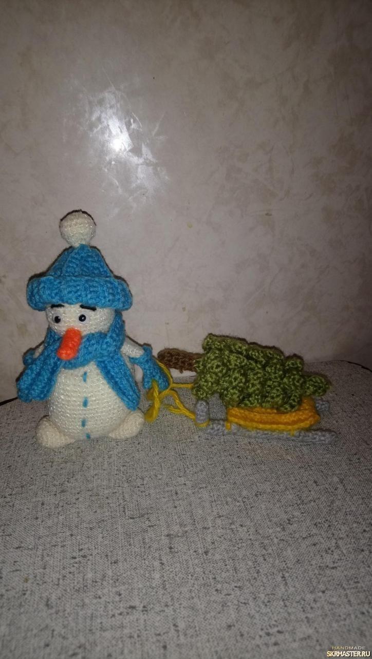 тут изображено снеговик с санями и елкой