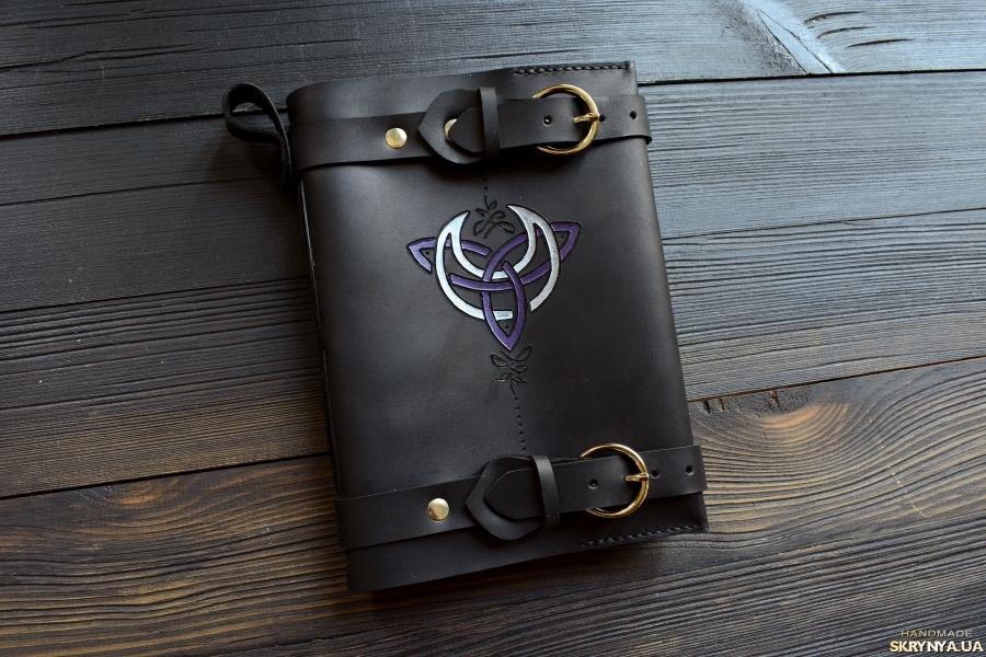 тут изображено Шкіряний блокнот Книга тіней з символом Богині та трискеліоном